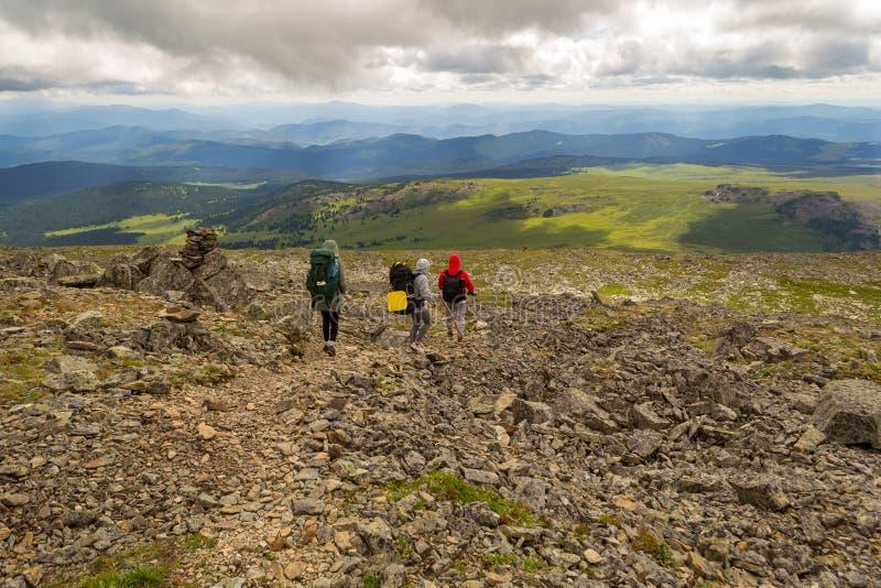3 туриста 2 девушки и один мальчик с рюкзаками идут вниз с стоковое изображение