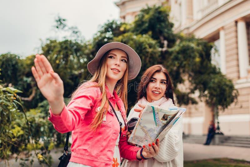 2 туриста женщин ища для правого пути используя карту в Одессе оперным театром Счастливый указывать путешественников друзей стоковое фото