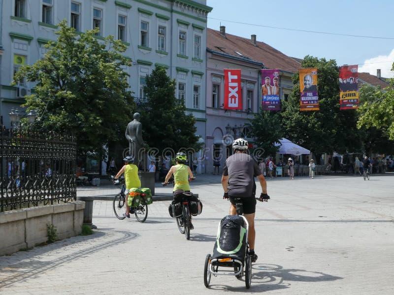 3 туриста людей наслаждаются их каникулами, ехать их велосипеды вниз с главной улицы внутри стоковые фото