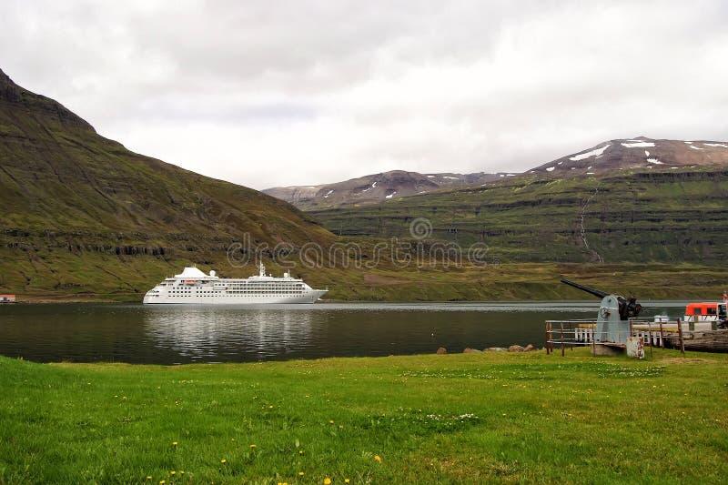 Туристическое судно в фьорде Sejdisfjordur, Исландии Океанский лайнер в гавани моря на ландшафте горы Курсировать для удовольстви стоковое изображение