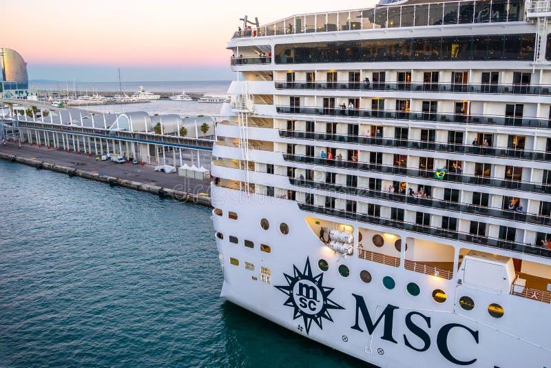 Туристическое судно фантазии MSC состыкованное на терминале порта круиза Барселоны на заходе солнца с гостиницой w Барселоны в пр стоковые изображения rf