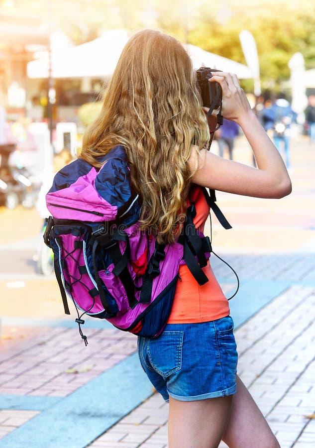 Туристская девушка с рюкзаком фотографируя на цифровой фотокамере стоковые фотографии rf