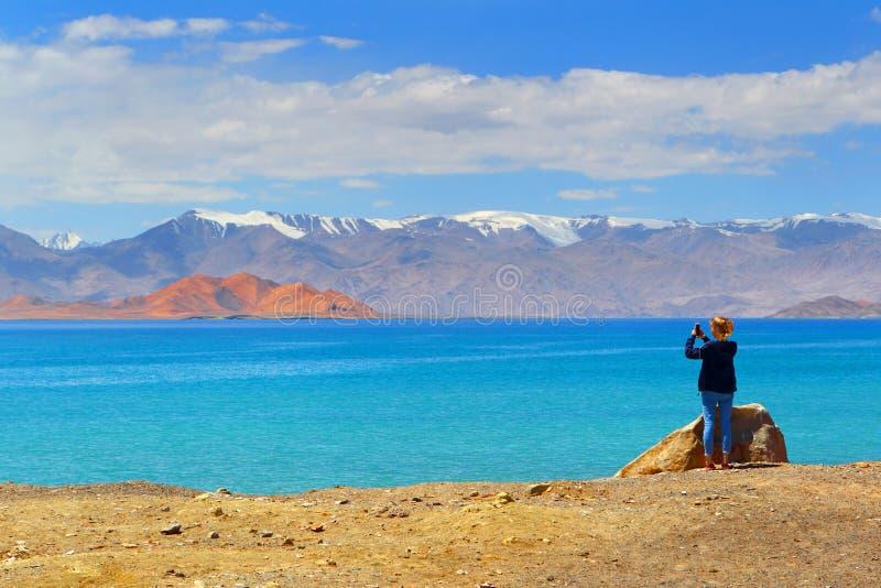 Туристская девушка фотографируя ландшафт горы по телефону пока путешествующ стоковые фотографии rf