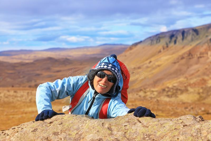 Туристская женщина взбираясь на горе стоковая фотография
