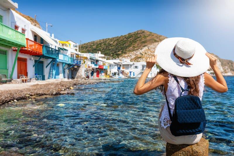 Туристская женщина наслаждается взглядом к рыбацкому поселку Klima, Milos, Греции стоковое изображение rf