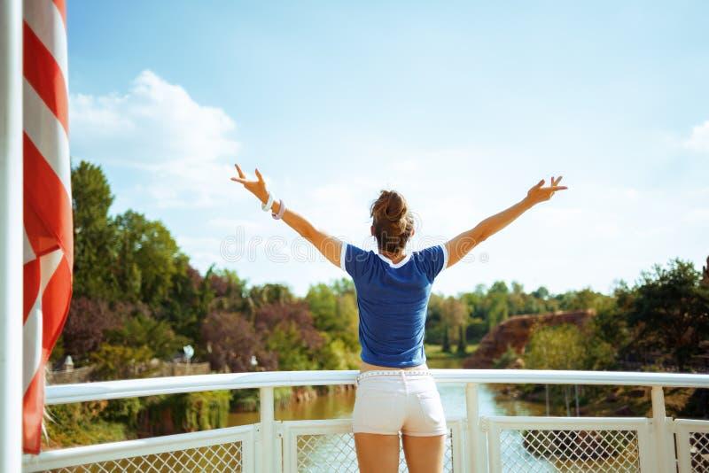 Туристская женщина на лодке радуясь пока имеющ круиз реки стоковое фото rf