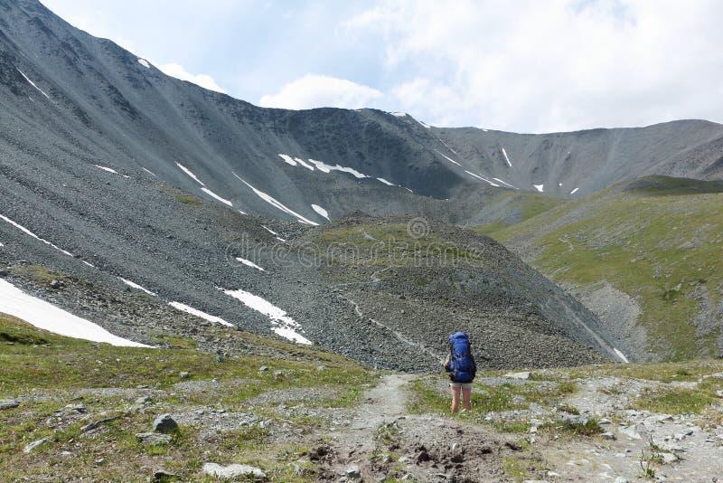 Туристская женщина приходя вниз от пропуска Kara-Turek, Altai Mounta стоковые фото