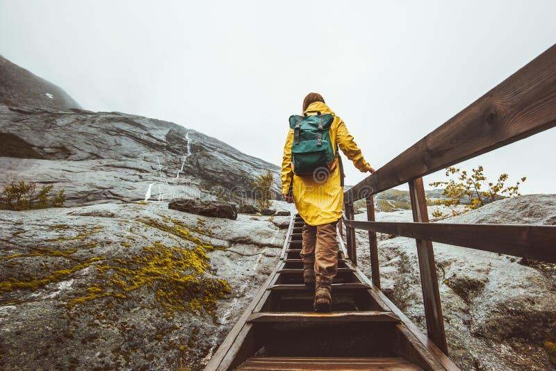 Туристская женщина при рюкзак взбираясь вверх лестницы в скалистых горах стоковая фотография rf