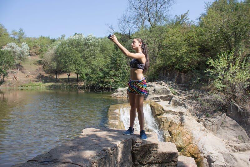 Туристская маленькая девочка внутри outdoors Принимающ автопортрет с камерой позвоните по телефону после пешего туризма к неимове стоковые изображения rf