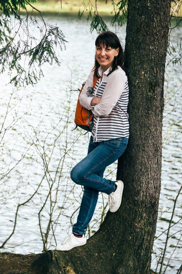 Туристская молодая усмехаясь девушка при оранжевый рюкзак стоя близко к большому дереву на банке озера горы стоковая фотография