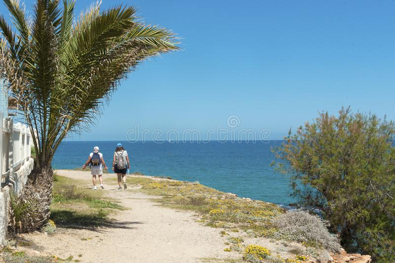 Туристская прогулка вниз с дорожки вдоль моря стоковое фото rf