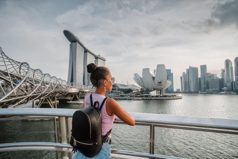 Туристские взгляды девушки на неимоверно красивом виде залива Сингапура Городской пейзаж азиатской метрополии Современные здания  стоковые фотографии rf
