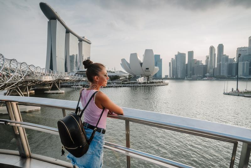 Туристские взгляды девушки на неимоверно красивом виде залива Сингапура Городской пейзаж азиатской метрополии Современные здания  стоковые изображения