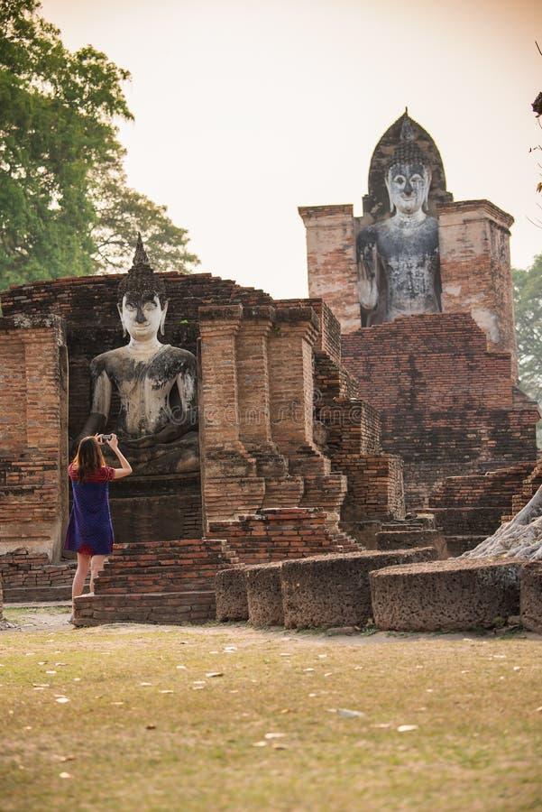 Туристские женщины принимают фото на парке Sukhothai историческом, виске Mahathat Sukhothai, Таиланд стоковое изображение