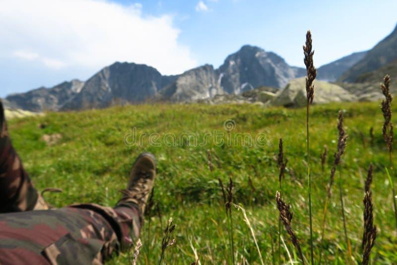 Туристские ноги отдыхая в горах с живописным взглядом Располагаясь лагерем и мотивационное изображение стоковое фото