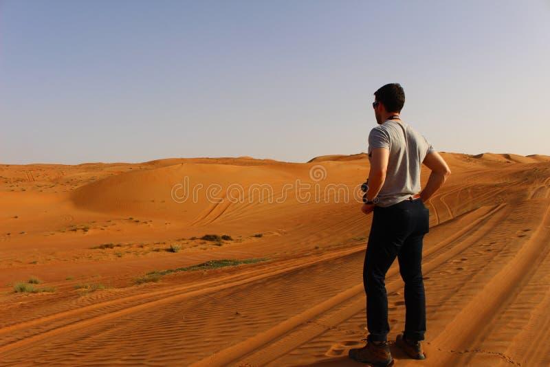 Туристские пристальные взгляды вне на необъятности песков Wahiba в Омане стоковые фотографии rf
