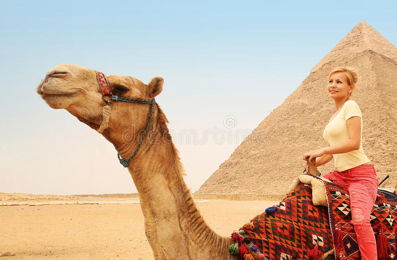 Туристский верблюд катания в Гизе Молодая белокурая женщина около пирамиды стоковые изображения