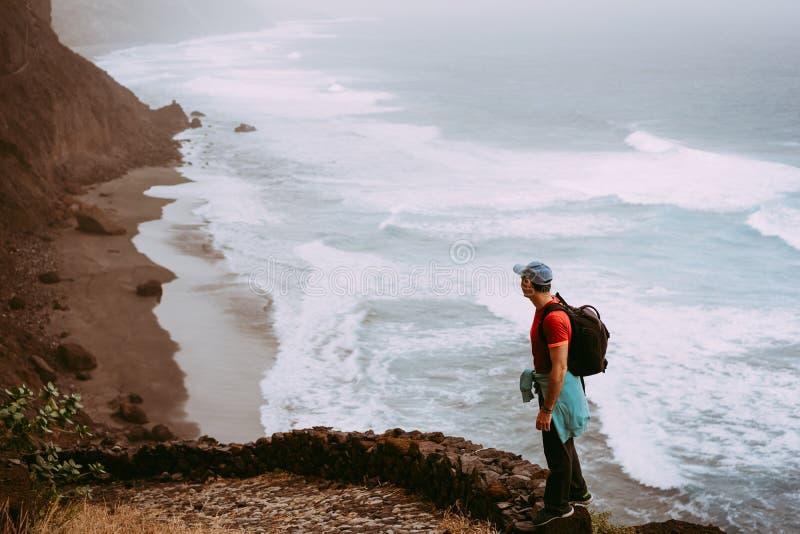 Туристский идя долгий путь вдоль береговой линии скалы с океанскими волнами от Cruzinha к к Ponta делает Sol Огромные горы на стоковое изображение rf
