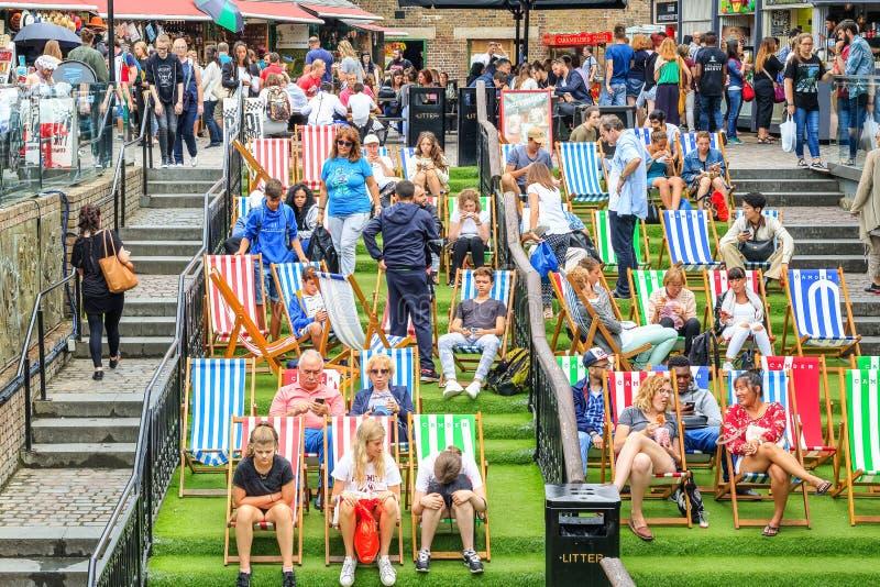 Туристский ослаблять на deckchairs на толпить рынке Camden в Лондоне стоковые фотографии rf