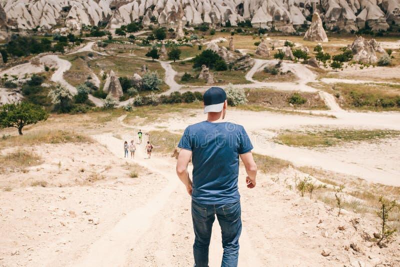 Туристский парень пробует уловить вверх с его друзьями туристов на дороге в холмистой сельской местности Cappadocia внутри стоковое изображение