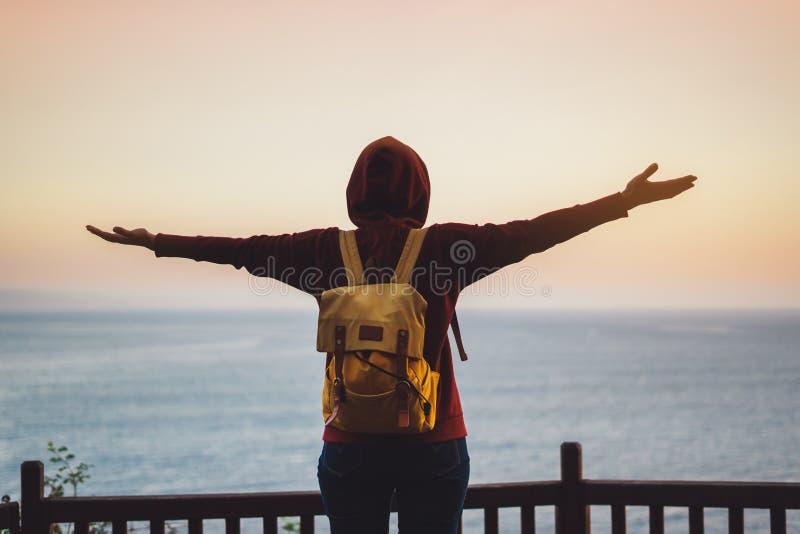 Туристский путешественник при рюкзак стоя с поднятыми руками, hiker смотря на заходе солнца к долине в отключении, наслаждаться м стоковое изображение