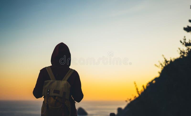 Туристский путешественник с рюкзаком на утре ослабляет время, hiker смотря на заходе солнца к долине в отключении, маленькую дево стоковое фото rf
