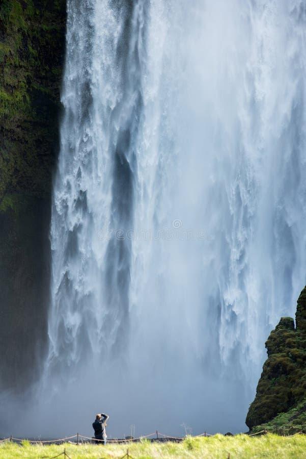 Туристский фотографируя водопад Skogafoss, Исландия стоковая фотография