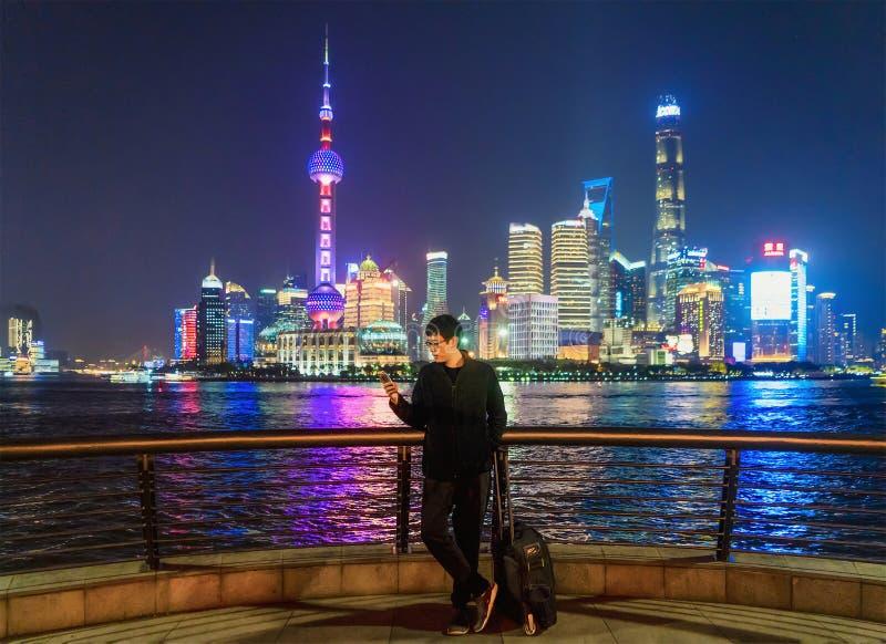 Туристский человек используя смартфон около бунда в центре города Шанхая, Китае в отключении перемещения, каникулах, или концепци стоковое изображение