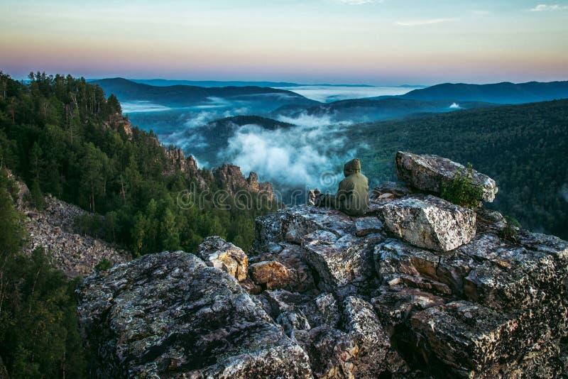 Туристский человек сидя назад на пике гор и наслаждается для того чтобы увидеть красивый взгляд ландшафта утесов и тумана приходя стоковые фотографии rf