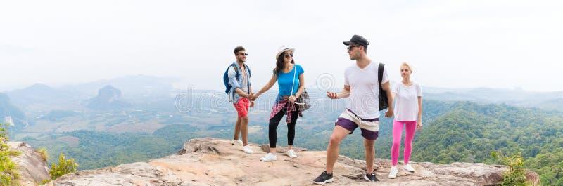 2 туристских пары с рюкзаком на говорить горы верхний над красивым взглядом панорамы ландшафта стоковое изображение