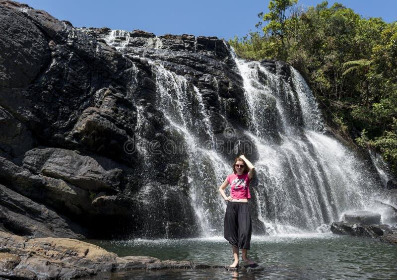 Туристское положение девушки около огромного изумительного красивого водопада стоковое фото rf
