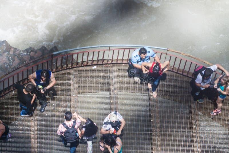 Туристы восхищают Iguacu Игуазу Фаллс стоковые фотографии rf