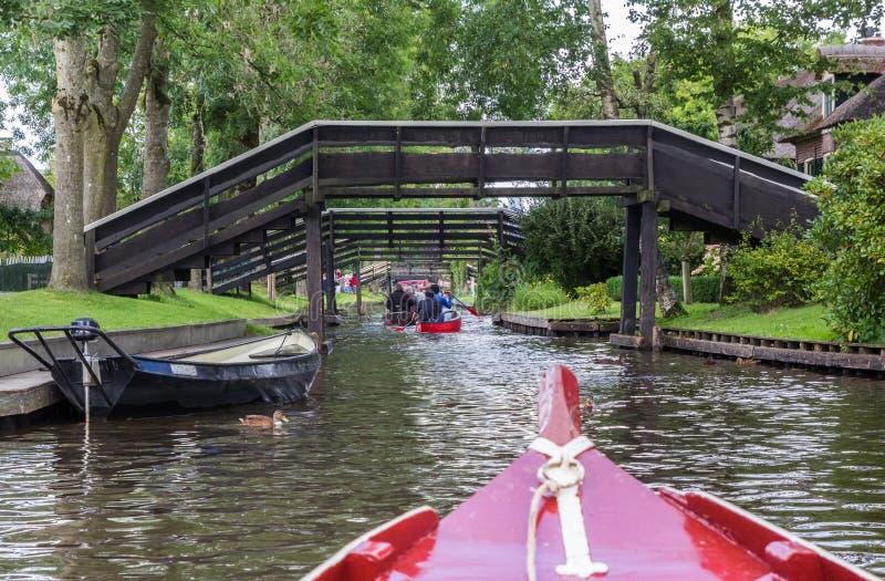 Туристы в маленьких лодках под мостами Giethoorn стоковые изображения