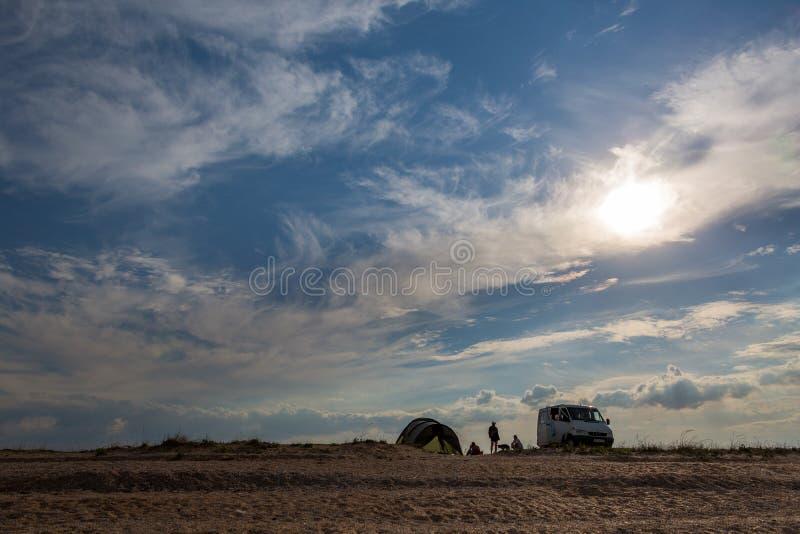 туристы в расположенной лагерем природе и сидеть на горизонте автомобили и шатры стоковая фотография rf