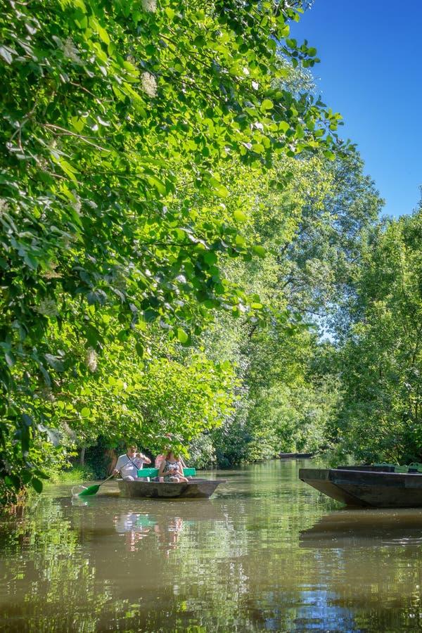 Туристы в rowboat на канале воды посещая зеленую Венецию в Зеленой Венеции Франции стоковые изображения rf