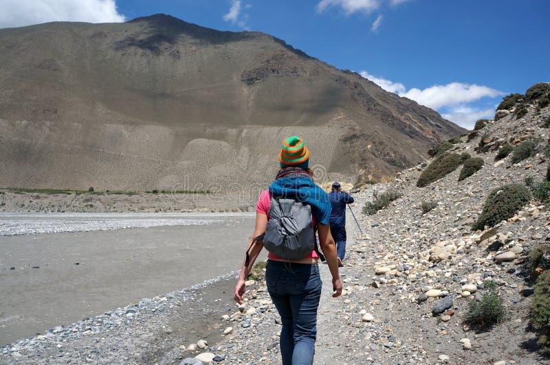 Туристы идут вдоль банков реки Kali Gandaki, против фона гималайских гор стоковая фотография rf