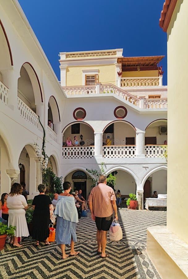 Туристы и посетители внутри монастыря Panormitis стоковые фото