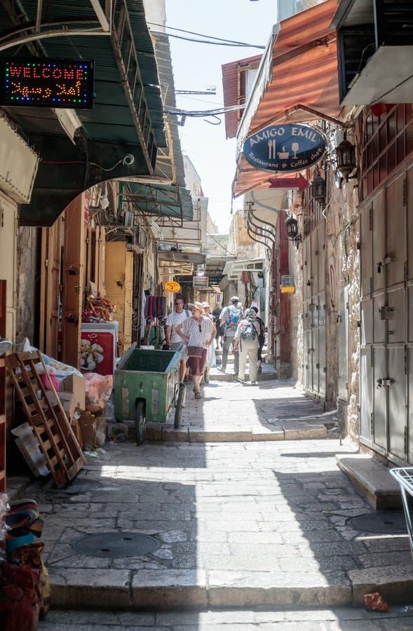 Туристы идут вниз с через улицу dolorosa в старом городе Иерусалима, Израиля стоковое изображение