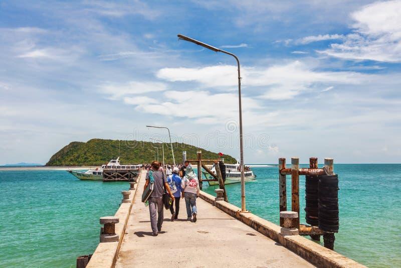 Туристы идут вдоль пристани к шлюпке стоковое изображение rf