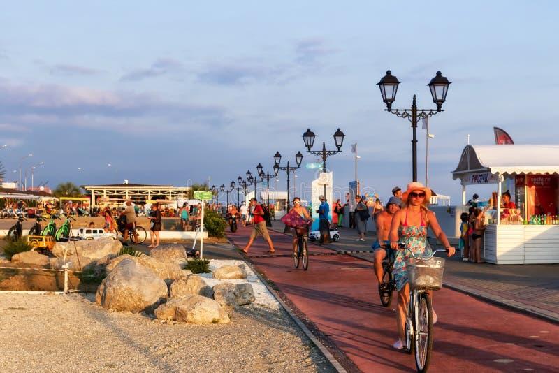 Туристы идут и едут на электрических циклах и велосипедах на prome стоковые изображения