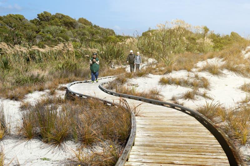 Туристы идя на деревянную дорожку пляжем на запасе Tauparikaka морском, Haast, Новой Зеландии стоковые фото