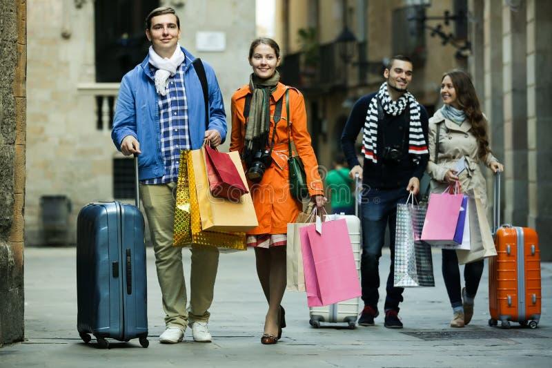 Туристы идя с хозяйственными сумками стоковые изображения