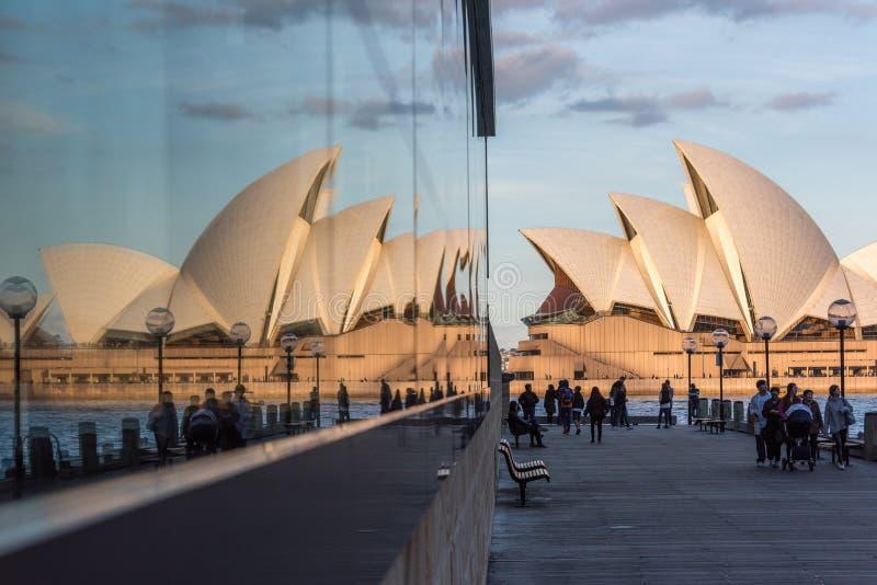 Туристы и locals идя с оперным театром Сиднея на предпосылке стоковое фото