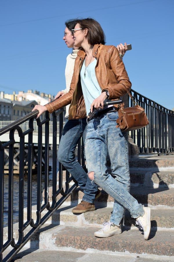 Туристы молодых дам стоят на обваловке реки Fontanka в Санкт-Петербурге России и зданиях дозора на противоположной стороне стоковые изображения rf