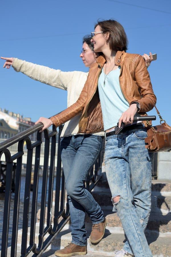 Туристы молодых дам стоят на обваловке реки Fontanka в Санкт-Петербурге России и указать на ориентир стоковое изображение rf