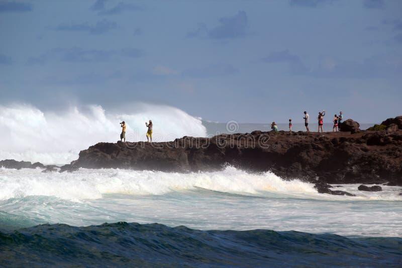 Туристы наблюдая опасные океанские волны зимы стоковое изображение