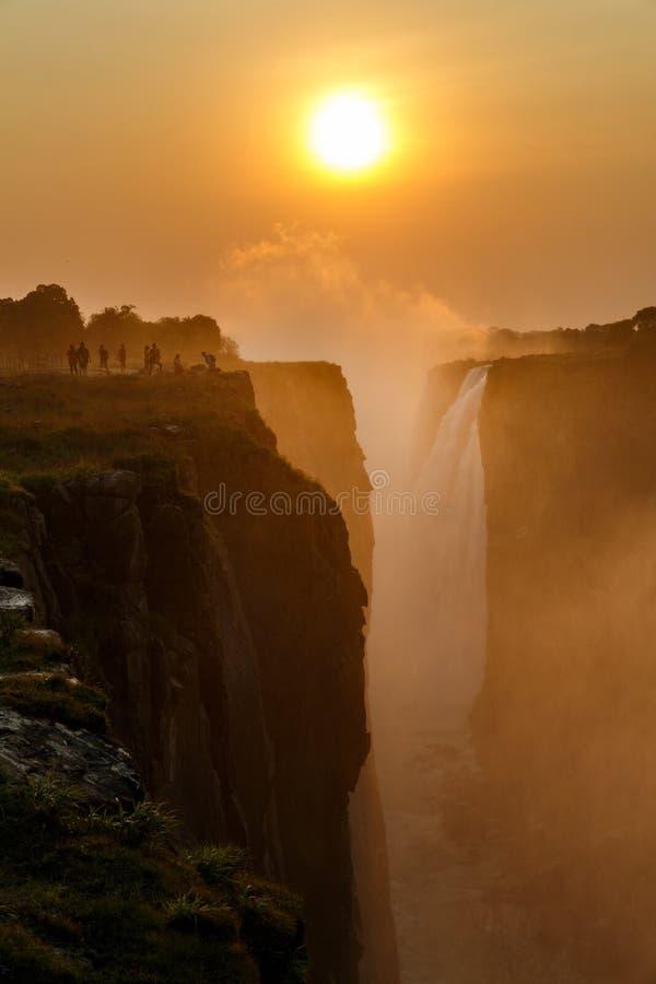 Туристы наслаждаются заходом солнца Victoria Falls с апельсином стоковые фотографии rf