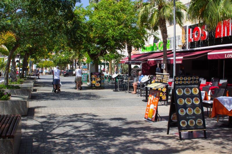 Туристы на дереве выровняли бульвар с магазинами и кафами в Playa de Las Америках в острове Teneriffe стоковые изображения
