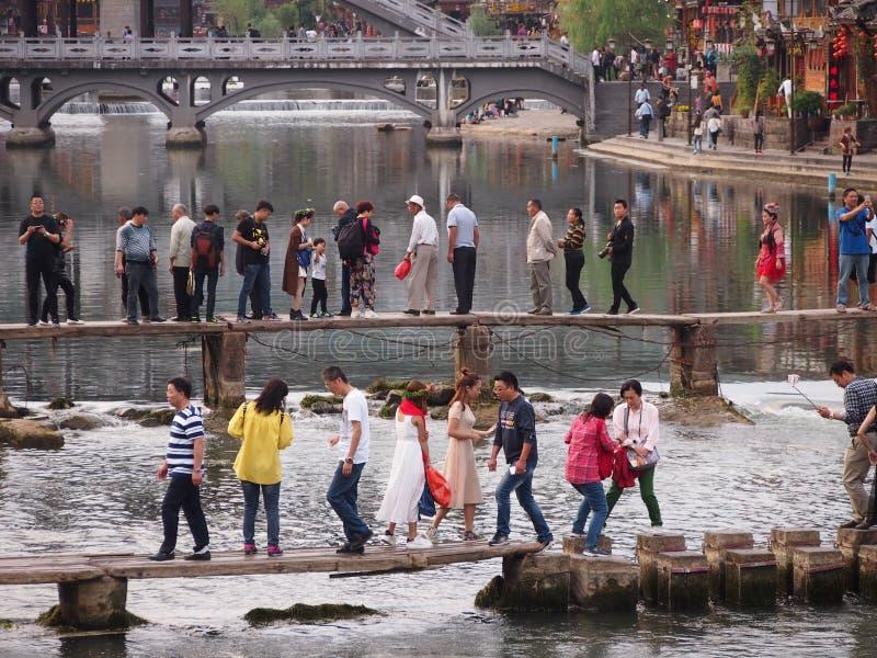 Туристы на узком мосте в Fenghuang стоковое изображение rf