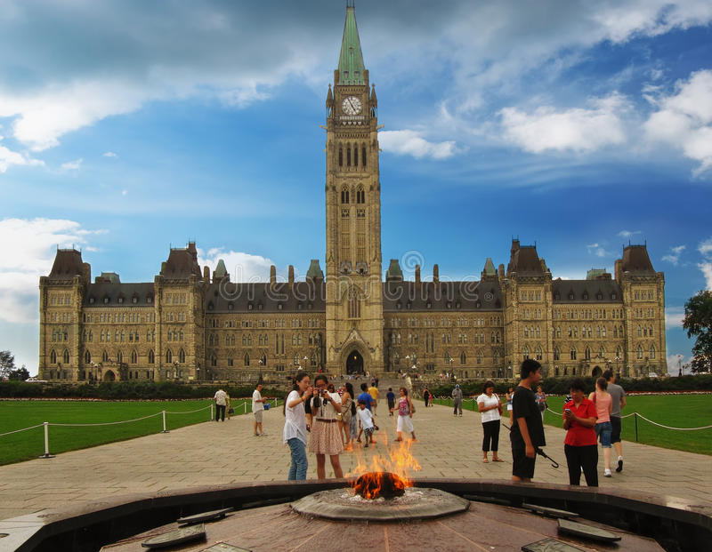 Туристы около Centennial пламени перед главным образом парламентом здания Канады стоковое изображение